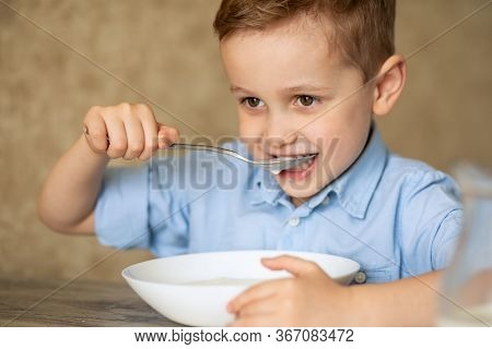 Adorable Caucasian Child With Brown Eyes And Red Blond Hair Eats Porridge Himself. The Boy Bit His S