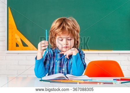 Elementary School And Education. Portrait Of Pupil Of Primary School Study Indoors. After School Tea