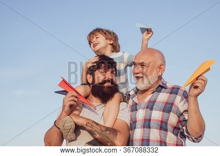 Grandfather With Son And Grandson Having Fun In Park. Fathers Day Concept. Cute Child Hugging His Fa