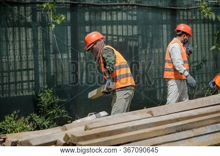 Asian Construction Workers On A Construction Site In Bucharest.