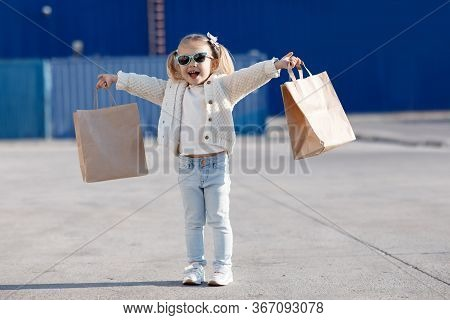 Cheerful Baby With Purchases. Little Girl Holding Shopping Bags.little Girl Alone In Spring Outdoors