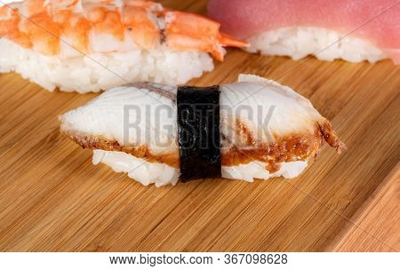 Sushi With Eel, On A Bamboo Leaf. In The Background Sushi With Shrimp And Sushi With Tuna.