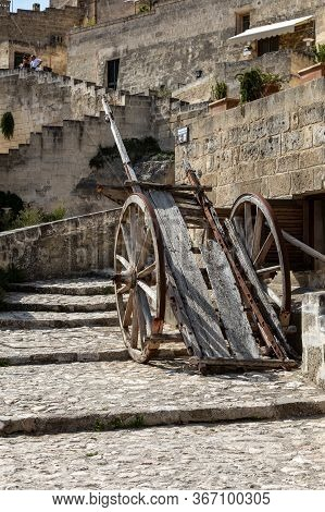 Matera, Italy - September 15, 2019: Typical Cobbled Stairs And Old Wooden Cart In A Side Street Alle