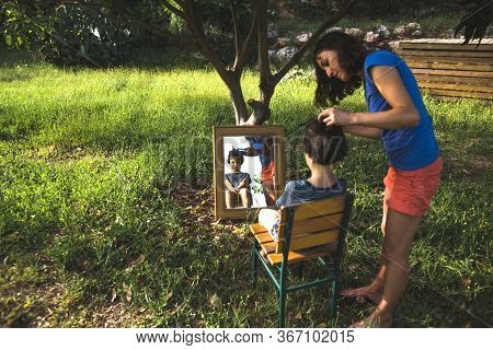 A Woman Cuts The Hair Of A Child In The Yard Of The House, Mom Cuts Her Son's Hair Near The House, F