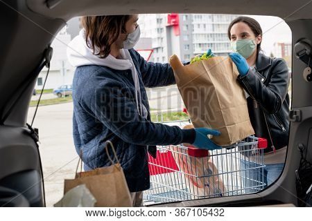 Young wife giving paperbag with fresh food products to her husband standing by open car trunk while putting bags in car