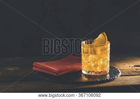Glass Of The Cocktail Negroni With Red Napkin And Black Stone Tray On A Old Wooden Board. Decorated