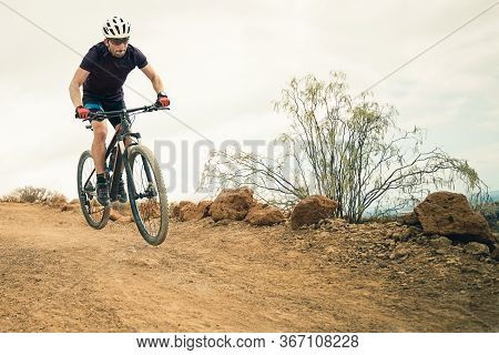 Cyclist In Violet T-shirt Riding A Mountain Bike. Man On Mountain Bike Rides On The Trail On A Storm