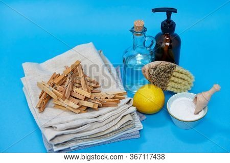 natural cleaning stuff and eco living concept - washing soda, lemon, bottle of vinegar, liquid soap and brush with wooden clothespins on canvas towels over blue background