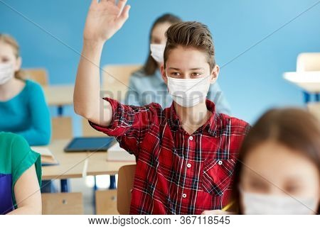 education, healthcare and pandemic concept - student boy wearing face protective medical mask for protection from virus disease with raised hand at school lesson