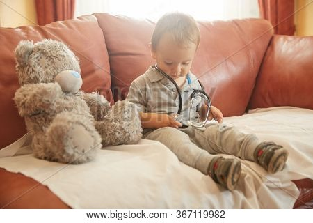 Funny Cute Pensive Boy Child Playing With Stethoscope. Playful Toddler Sit On Armchair Dreaming Be P