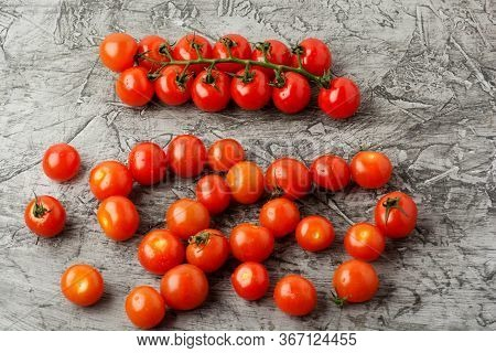 Group Of Cherry Tomatoes On A Gray Concrete Background. Ripe And Juicy Cherry Tomatoes.
