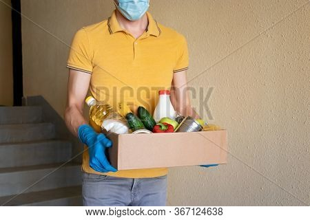 Man In Protective Mask And Gloves Holds Box Of Food. Donation Box With Food Supply, Canned Food, Cer