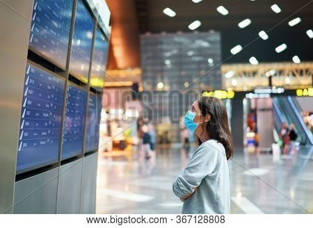 Woman In Virus Protection Face Mask Looking At Information Board Checking Her Flight In Internationa