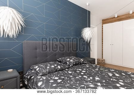 King Size Bed With Patterned Bedding, Two White Lamps And White Wardrobe
