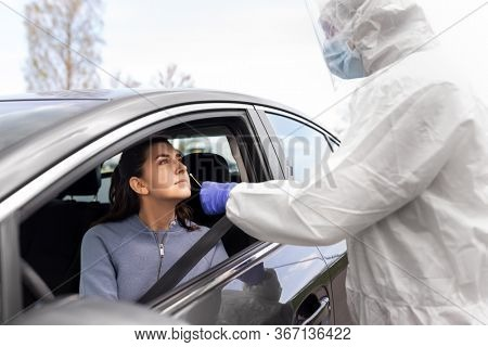 medicine, quarantine and pandemic concept - doctor or healthcare worker in protective gear or hazmat suit with beaker and cotton swab making coronavirus test for young woman in her car