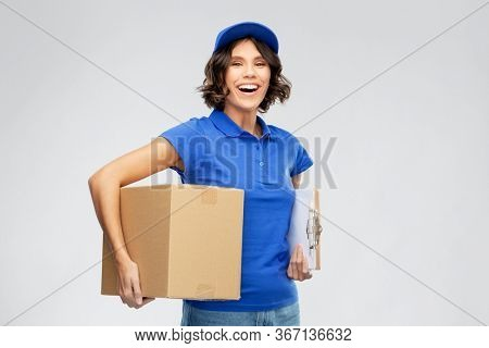 mail service and shipment concept - happy smiling delivery girl in blue uniform with parcel box and clipboard over grey background