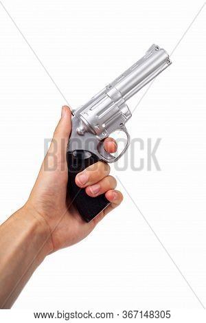 Hand Holding Up A Silver Revolver Pulling The Trigger, Gun In Hand Facing Up Symbol. Wild West Handg