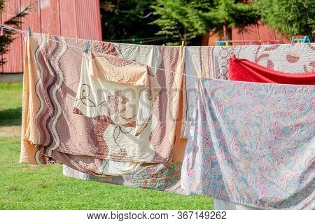 Simple Shot Of Laundry Hanging, Large Bed Set Bedding And Clothes Hanging On Wires On A Sunny Day, S