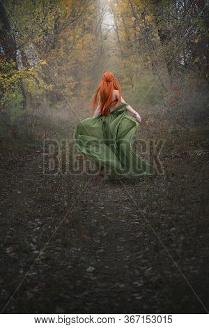 A Long-haired Red-haired Elf Girl Runs Away Into The Distance Through The Misty Autumn Forest. A Fai