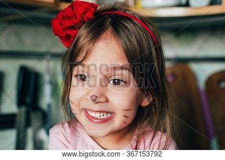 Portraite Of Cute Toddler Girl With Face Painting Like A Cat Smiling In The Kitchen. Real Life Momen