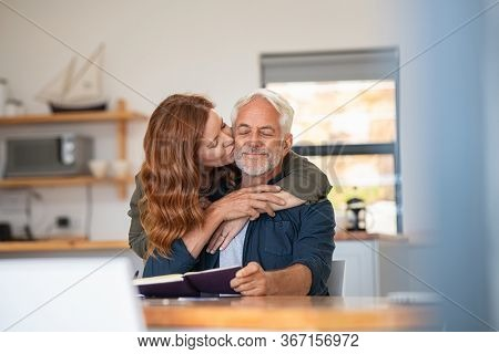 Happy loving woman kissing old man on cheek at home. Beautiful mature wife kissing her husband with beard and closed eyes. Senior couple in love.