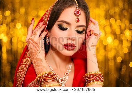 Portrait Of Beautiful Indian Girl In Red Bridal Sari Over Golden Bokeh. Young Hindu Woman Model With