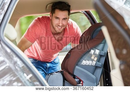 Man assembles a child seat in the back seat in the car before the holiday trip