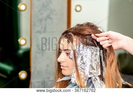 Hairstylist Colors Hair Of Woman With Foil In Beauty Salon.