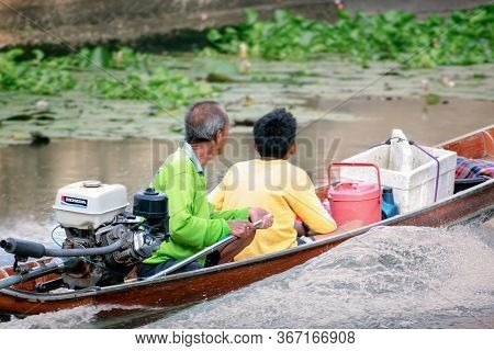 Bangkok, Thailand - May 16: Unidentified Old Man And A Boy Cruises Through The Canal Of Phasi Charoe