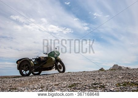 An Old Soviet Motorcycle With A Sidecar Stands Against The Sky With Clouds On The Stones. Green Colo
