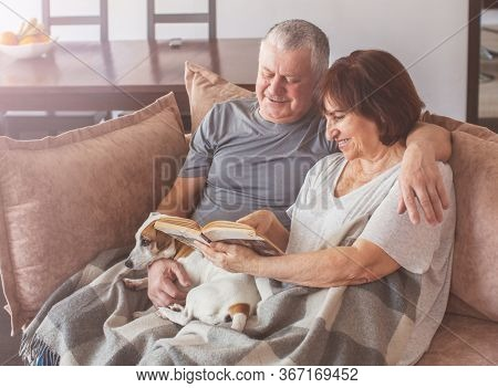Happy elderly couple sitting on sofa, reading book at home. Seniors with dog