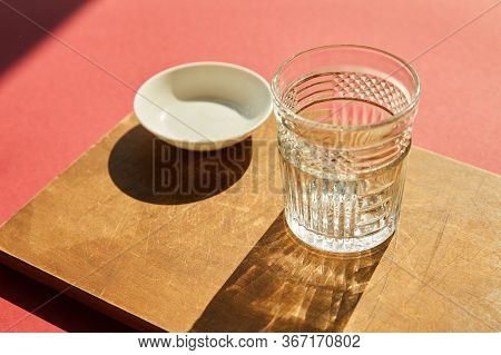 Faceted Empty Glass And White Bowl On Wooden Board In Sunlight