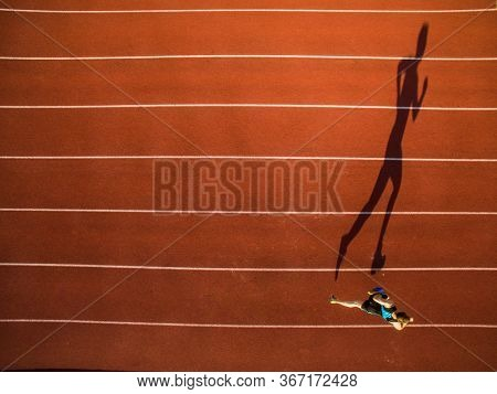 Shot of a young male athlete training on a race track. Sprinter running on athletics tracks seen from above