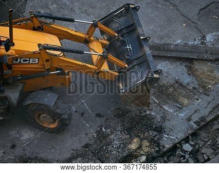 Kharkov, Ukraine - May 2020. Hydraulic Excavator Removing Remains Of Asphalt. Road Reconstruction. P