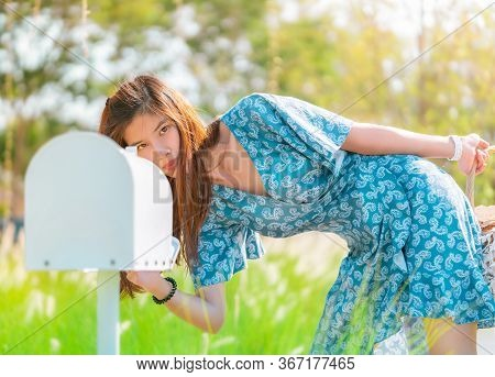 Pretty Asian Woman Is Checking Her White Mail Box In A Country Farm House Field.