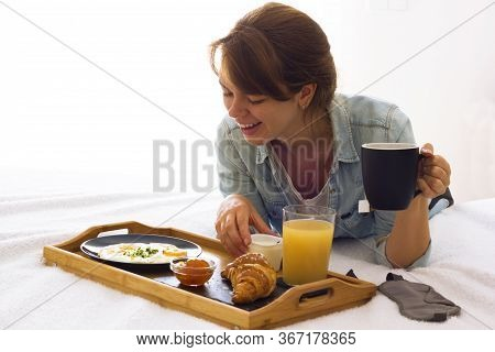 Happy Excited Young Woman Having Breakfast Holding A Coffee Or Tea Cup Lying On The Bed And Looking