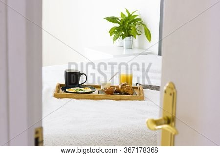 Opened White Door To Bedroom Interior With Bed, Plant And Decorative Set Of Breakfast On The Bed. Co