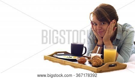 Happy Girl Having Breakfast Lying On The Bed And Looking At The Camara. Space For Text. Good Morning