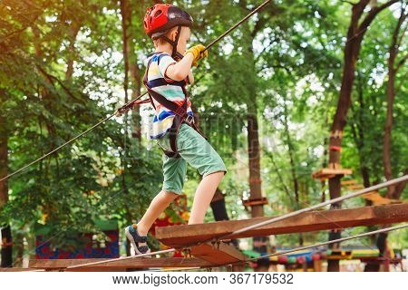 Kid Climbing In High Rope Course In Adventure Park. Kid In Safety Helmet, Extreme Sport. Summer Camp