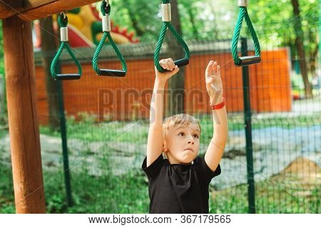 Cute Boy Playing On Monkey Bars. Kids Sport Outdoors. Summer Vacation, Camp And Leisure.
