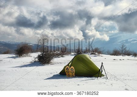 wild camp in tent on the snow of Nebrodi Park natural landmark in Sicily, on background blurred dramatic sky