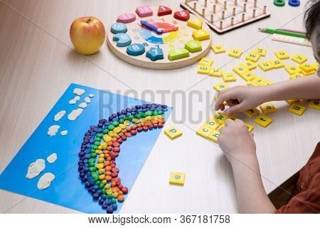 Child Is Studying, Playing At Home. Kid Puts Words From Letters. Only Hands Are Visible. At The Desk