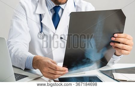 Close Up Of Male Doctor Hands Holding X-ray Scan. Physician With Stethoscope Examining X-ray Image.