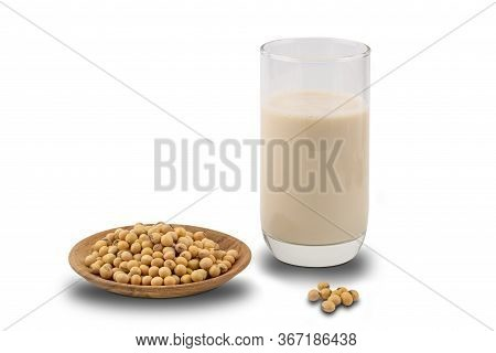 Soymilk In A Glass And Soy Beans In A Wooden Plate On White Background With Clipping Path.