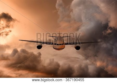 Jet Airliner flying through beautiful and dramatic sunset stormy and cloudy sky.