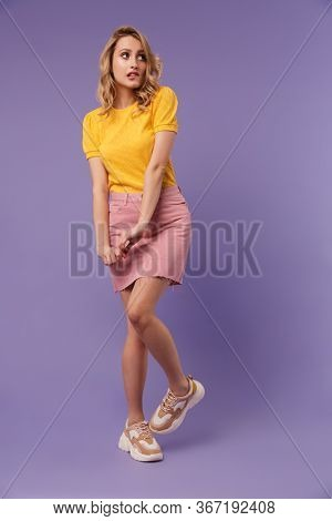 Full length image of nice scared woman posing and looking aside isolated over purple background
