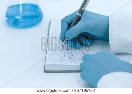 Close Up. Scientist Virologist Recording Test Results In A Journal.