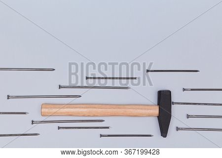 Hammer Instrument. Bunch Of Tacks Isolated On Blue Background. Handyman Tool. Renovation Concept. Co