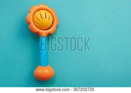 Plastic Toy Rattle In Bright Yellow Color With A Blue Handle. Plastic Retro Rattle. Baby Toys On Blu