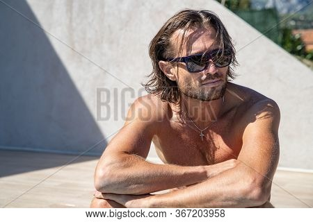 The Handsome Brutal Man In Sunglasses With A Long Hair And Naked Torso Sits Near The Pool, Lies At T